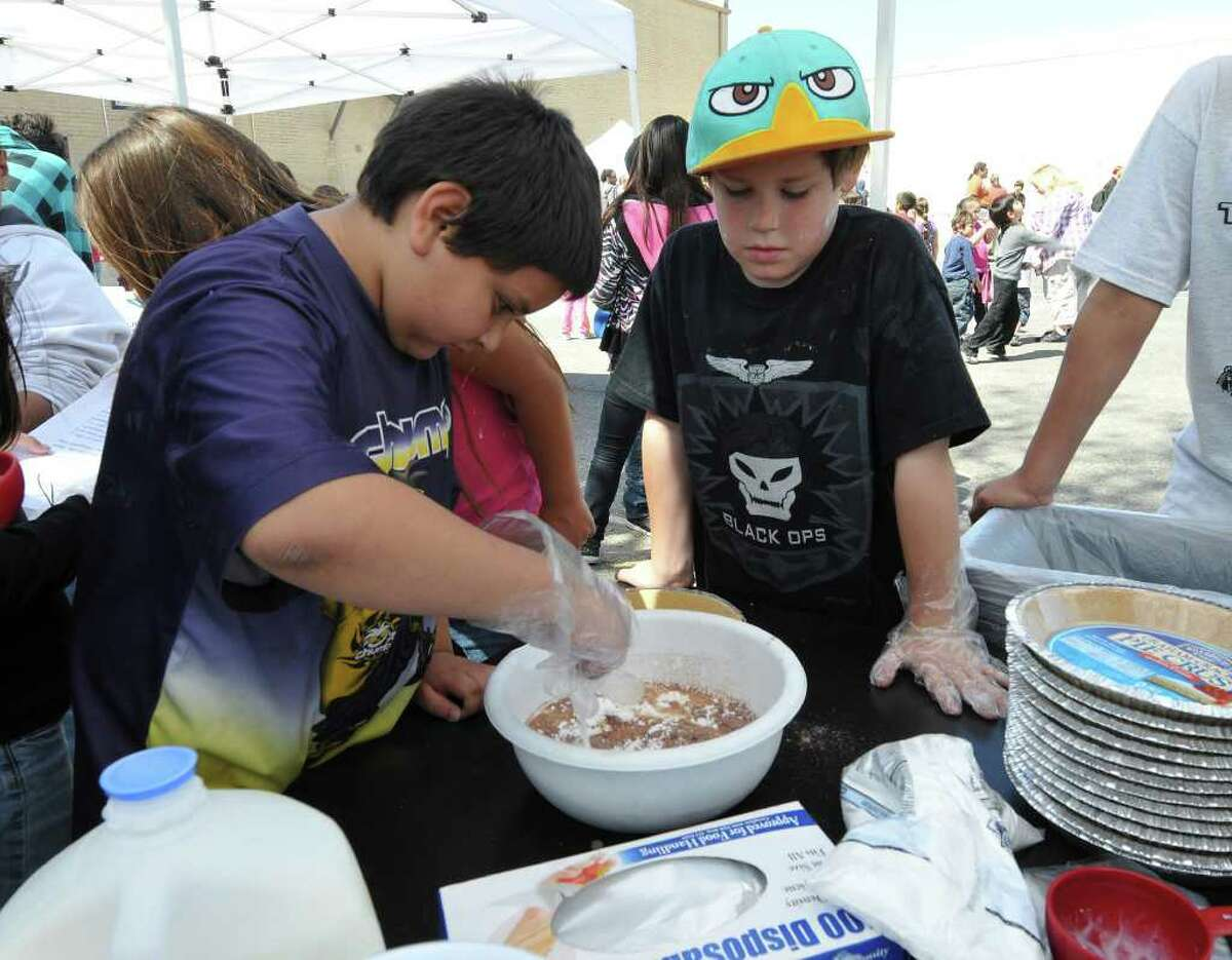 Noah Moreno (left) and Devin Longoria (right) mix ingredients for a pie during Pi Day festivities Friday at the San Antonio School for Inquiry and Creativity. Pi Day is observed March 14 (which this year falls during Spring Break) in honor of the mathematical constant pi, often rounded down to 3.14.