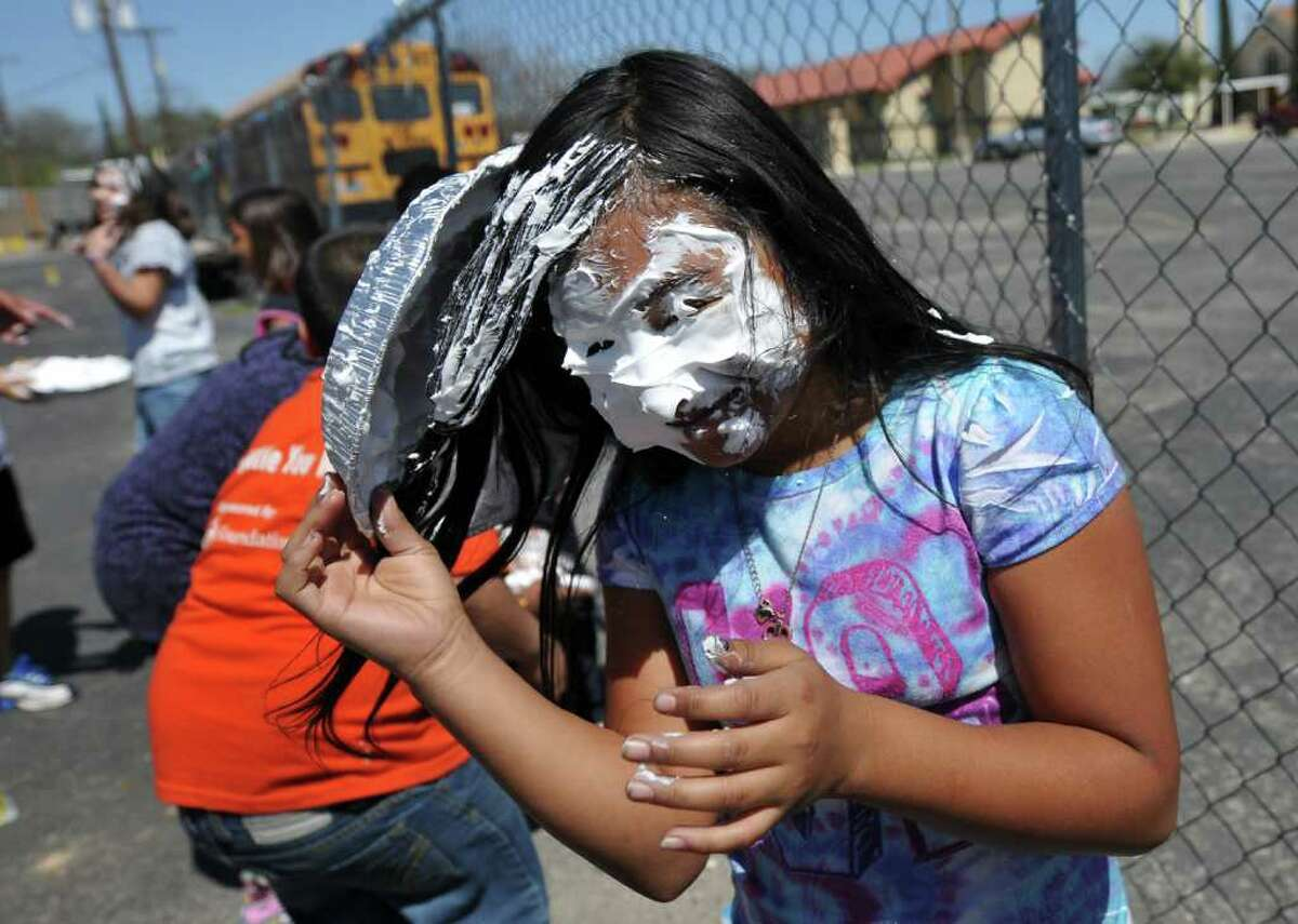 Andrea Adame recovers after being hit with a shaving cream pie during Pi Day festivities Friday at the San Antonio School for Inquiry and Creativity. Pi Day is observed March 14 (which this year falls during Spring Break) in honor of the mathematical constant pi, often rounded down to 3.14.