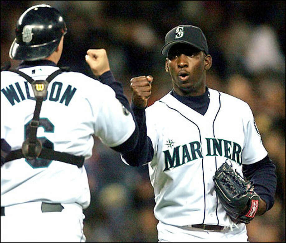 Dan Wilson gives Rafael Soriano a celebratory fist-bump after the rookie right-hander recorded his first save in the Mariners 7-2 victory. Soriano pitched three scoreless innings, allowing two hits. Photo: Paul Kitagaki Jr./Seattle Post-Intelligencer