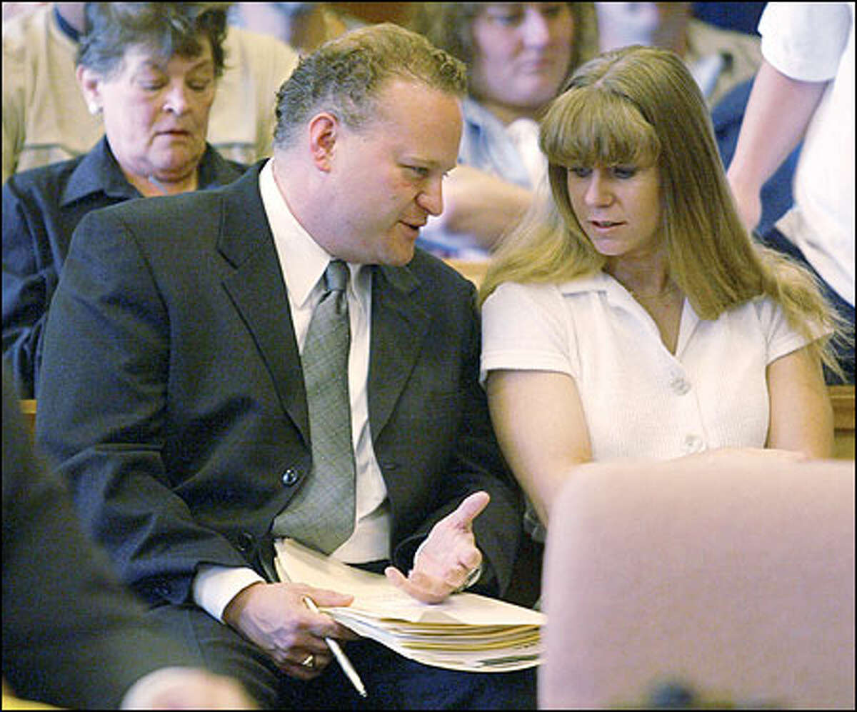 Former Olympic figure skater Tonya Harding speaks with her attorney Jon McMullen before appearing in the Clark County Courthouse in Vancouver, Wash., Monday, June 3, 2002, on drunk driving charges.