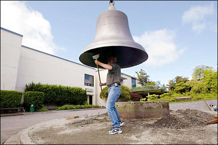 Chuck Easton sweeps the inside of the 112-year-old Seattle Fire Bell, which was moved yesterday to a new location in front of the Museum of History and Industry. Photo: Paul Kitagaki Jr./Seattle Post-Intelligencer