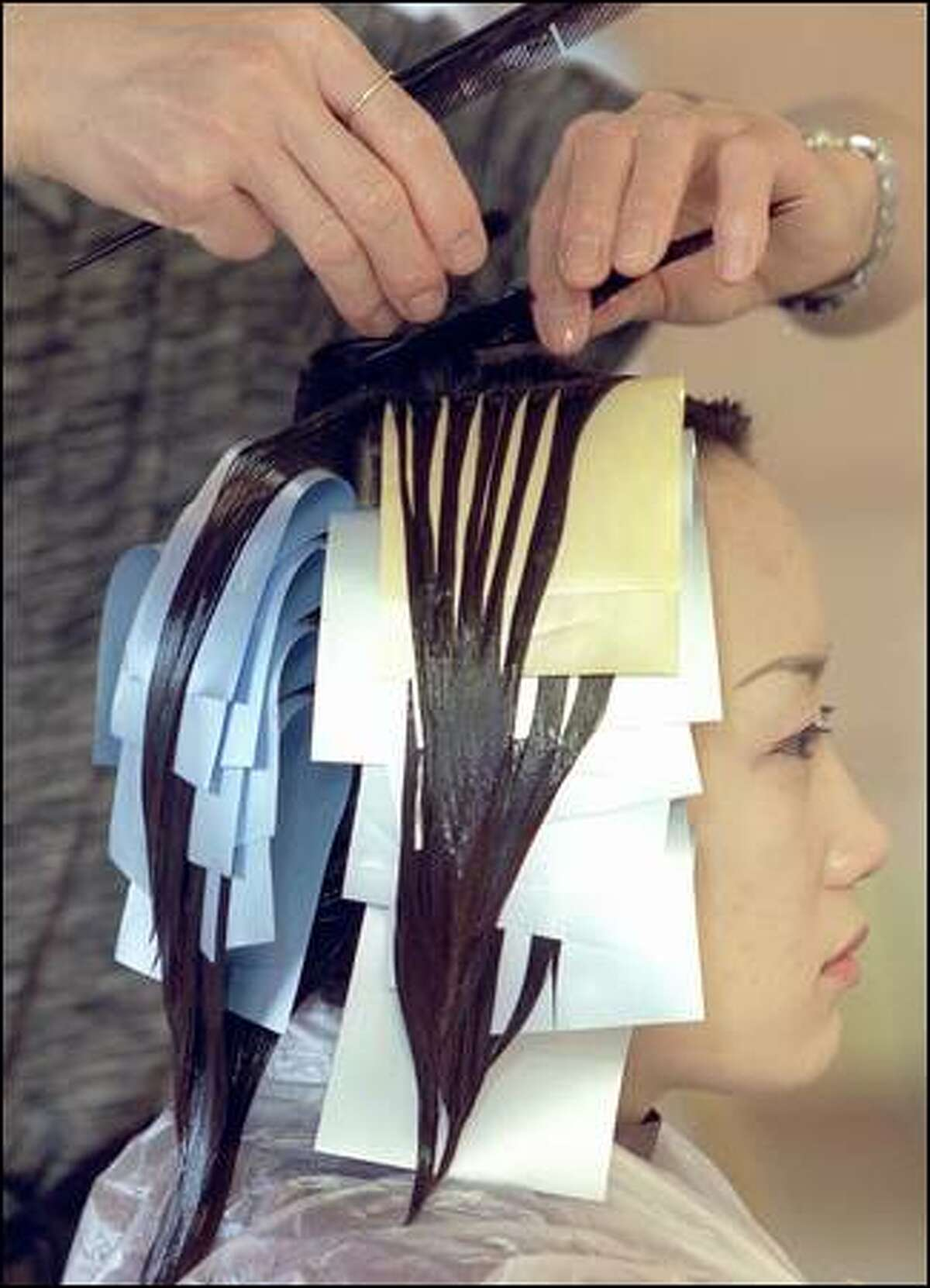 At Salon Juno at Uwajimaya Village, co-owner Juno Lee treats Hye-Jin's hair with straightening solution, which breaks the shaft's cystine bonds. Some stylists separate hair in layers across paper flaps, as shown, to give the roots a lift so that the resulting super-straight hair isn't completely flattened to the scalp.