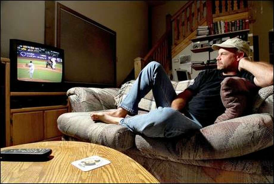 Don Pugh watches the Mariners play from the comfort of his home. Once a rabid Sonics fan, the Redmond resident turned his back on pro basketball because of rising ticket prices. Photo: Dan DeLong/Seattle Post-Intelligencer