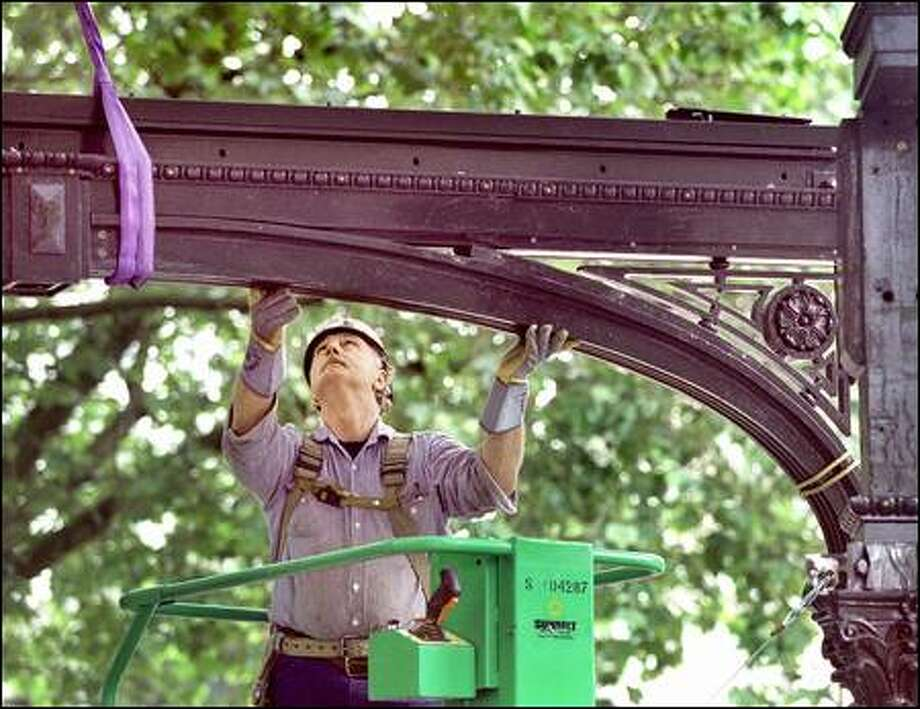 Larry Bluhn concentrates on placing the first piece of iron arch on top of two beams on the restored pergola in Pioneer Square. He delayed retirement to work on it. Photo: Renee C. Byer/Seattle Post-Intelligencer
