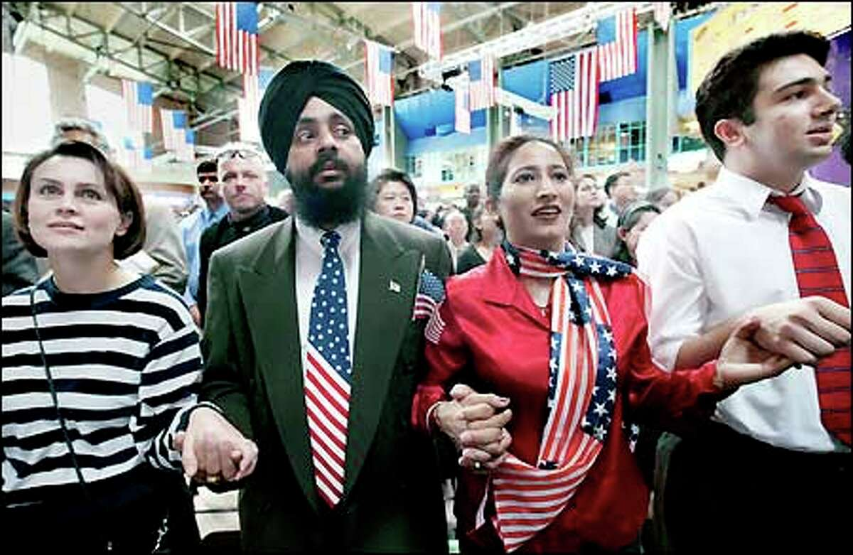 Karwinder Singh and his wife Ranjit Kaur, both of India, join hands with Tanya Motso, left, of Ukraine and Fahdad Fani of Iran as they are sworn in as new citizens at the Seattle Center yesterday.