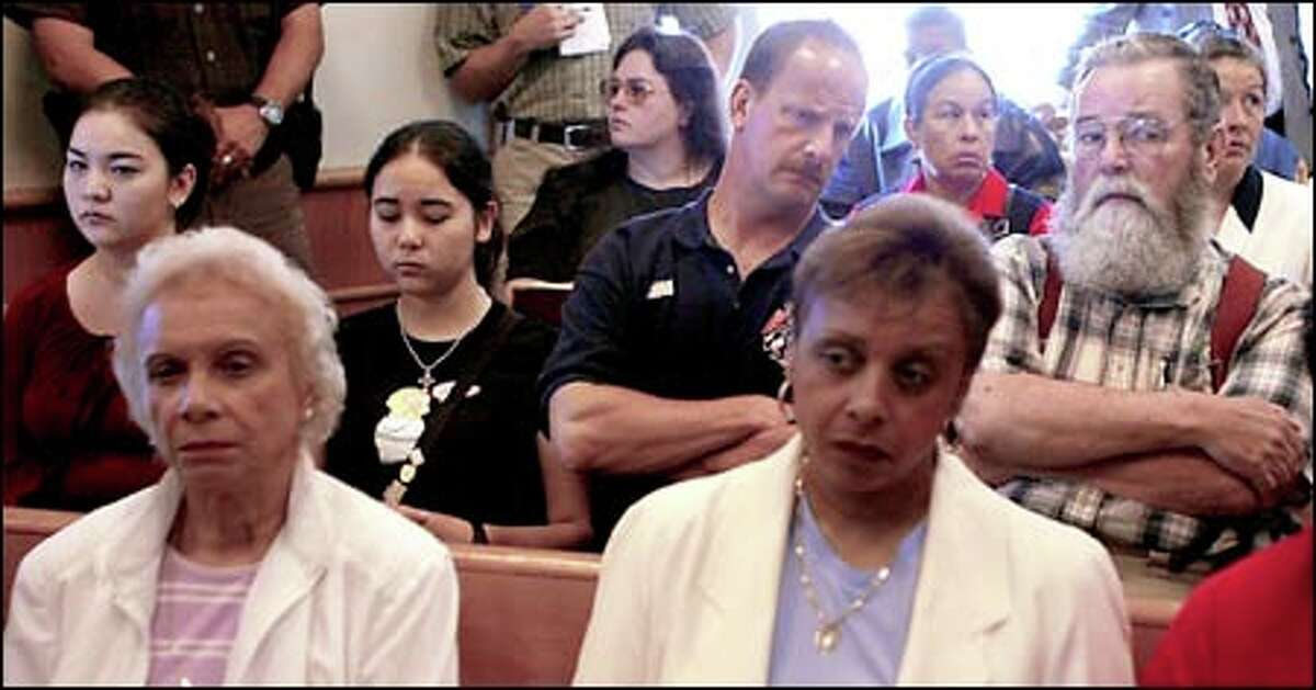 Geraldine Quarles, left front, the mother of Ronald Matthews, and Patricia Hampton, right, his sister, attend yesterday's hearing. Behind them are members of Deputy Richard Herzog's family.