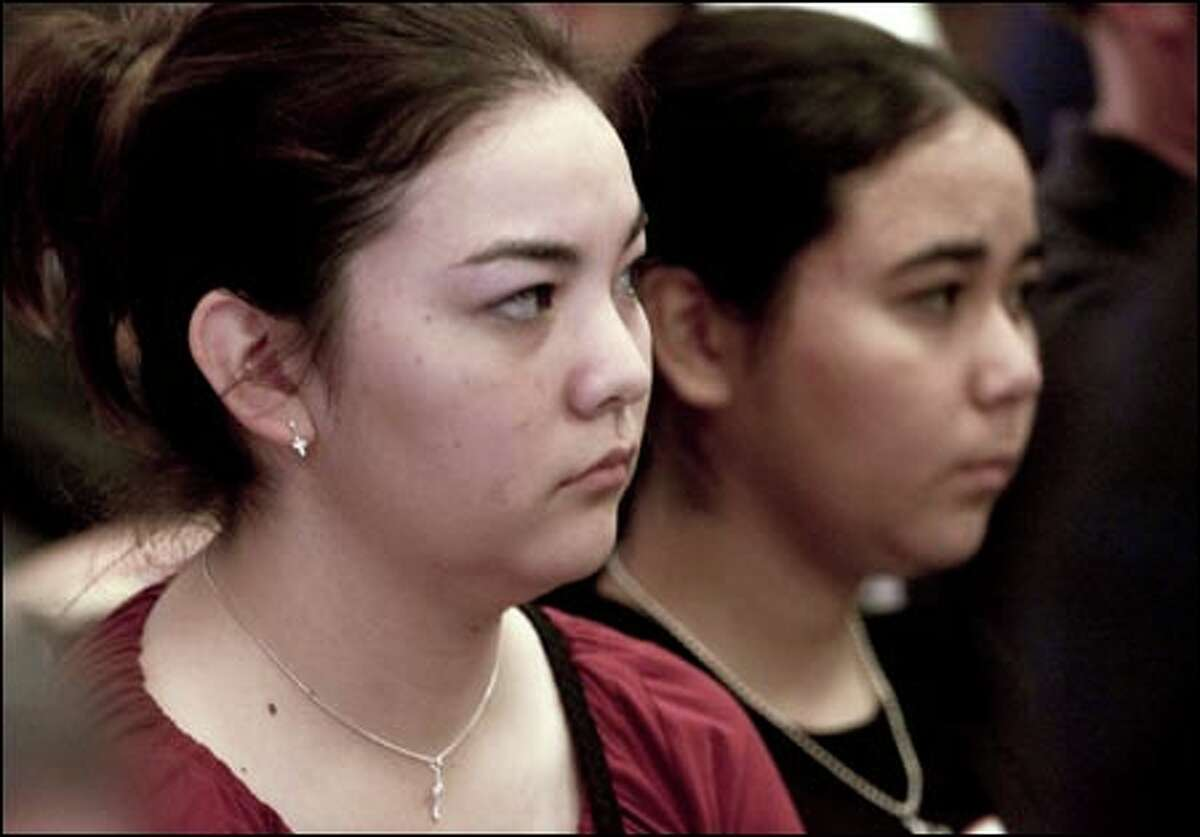 Deputy Richard Herzog's daughters, Sonja, left, and Erika, watch Ronald Matthews' arraignment yesterday at the King County Courthouse.