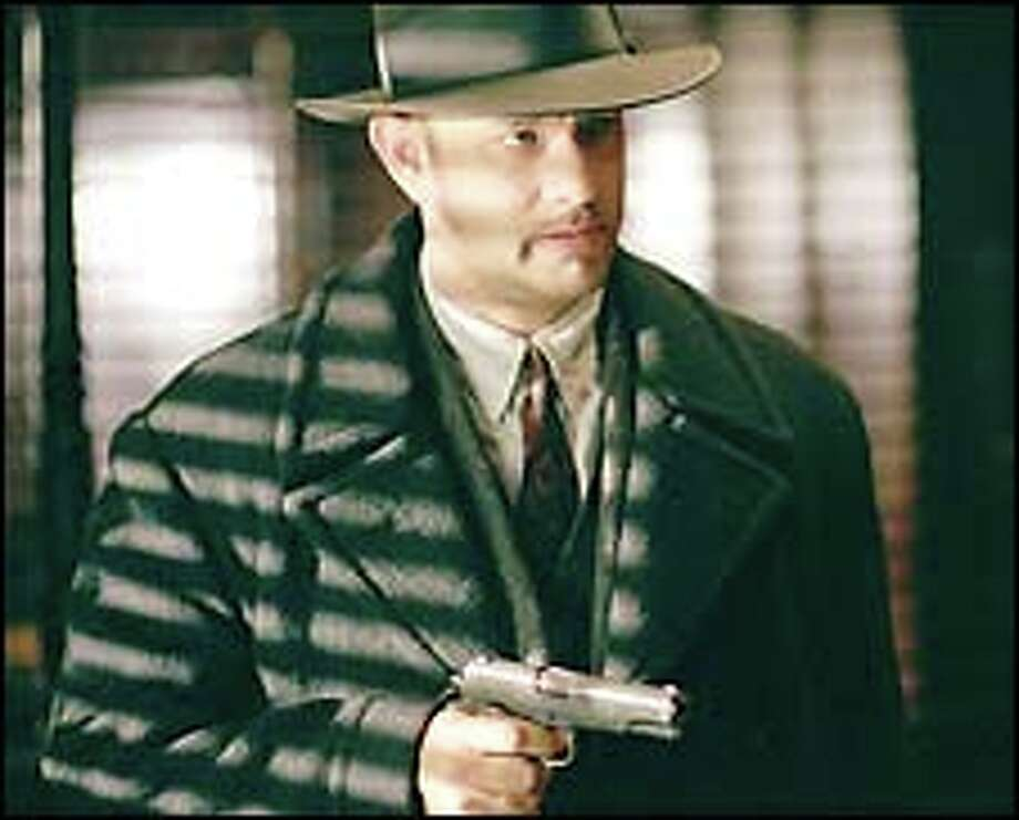 "Tom Hanks is a hit man trying to protect his son in ""Road to Perdition."""