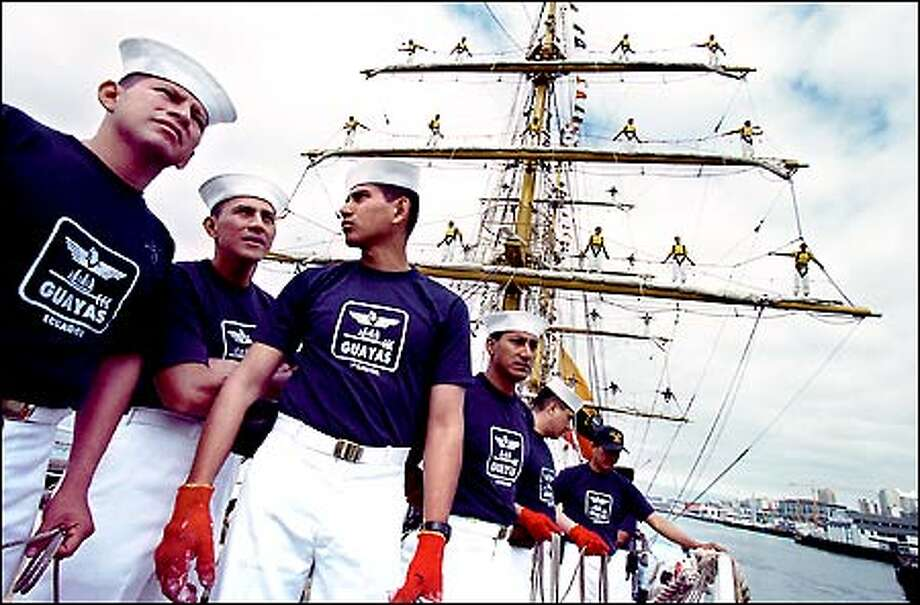 With fellow crewmen adorning the yardarms, sailors aboard Ecuador's tall ship Guayas prepare to tie up at Pier 56 in Seattle Thursday. The 257-foot Guayas, a training ship for the Ecuadorean naval academy, is a three-masted bark. Photo: Paul Joseph Brown/Seattle Post-Intelligencer