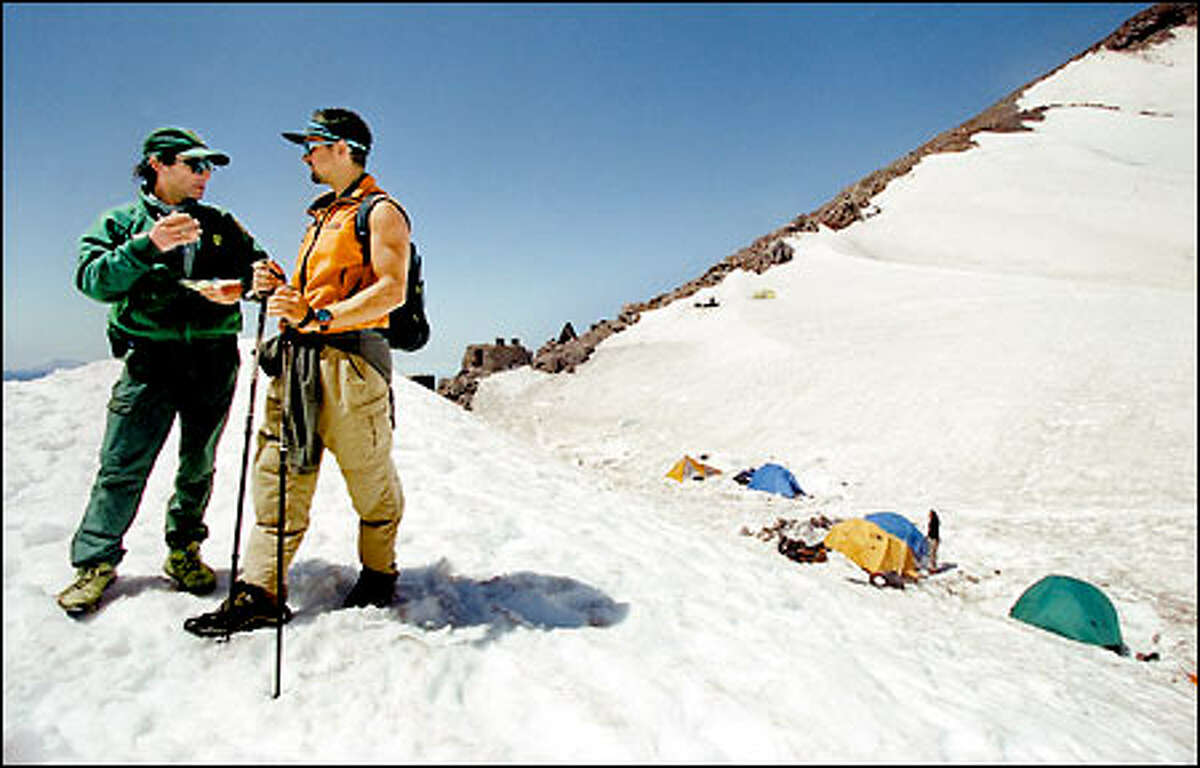 At 10,080-foot Camp Muir, Mount Rainier National Park climbing ranger Glenn Kessler, left, tells the ill-equipped and inexperienced Jesse Edkins of Monterey, Calif., why his attempt to climb the 14,411-foot mountain alone was a very bad idea. Rather than punish Edkins with a fine, the diplomatic Kessler chose to educate the novice about Rainier's diverse hazards.