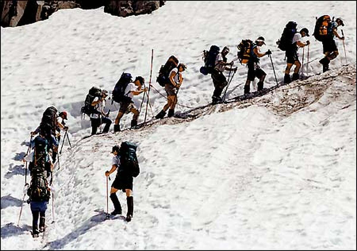 Climbers chug along the trail above Paradise in the early stage of their ascent to Camp Muir. With climbers attempting Rainier's summit in ever-growing numbers -- more than 11,000 tried last year -- there's no shortage of work for the park's 14 climbing rangers.