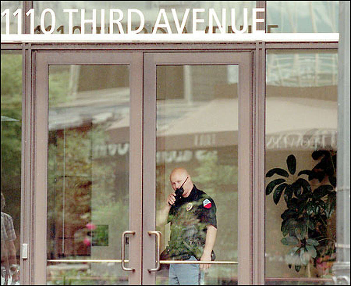 A security guard works inside a building housing Seattle FBI offices after police were called yesterday.