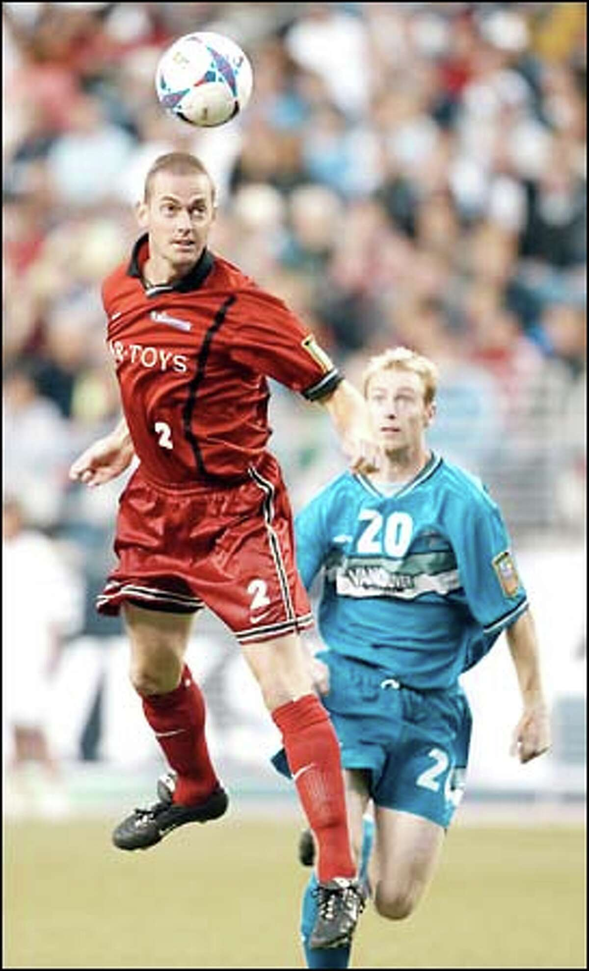 Sounders defender Scott Jenkins heads the ball away from Vancouver midfielder Dave Morris in first-half action at Seahawks Stadium.