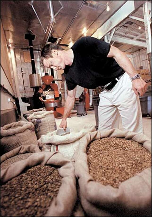 Jesse Sweeney blends coffee beans as his partner, Emanuele Bizzarri, roasts a batch of Caffe Umbria coffee. The two men started the business in March and have steadily increased production. Photo: Phil H. Webber/Seattle Post-Intelligencer
