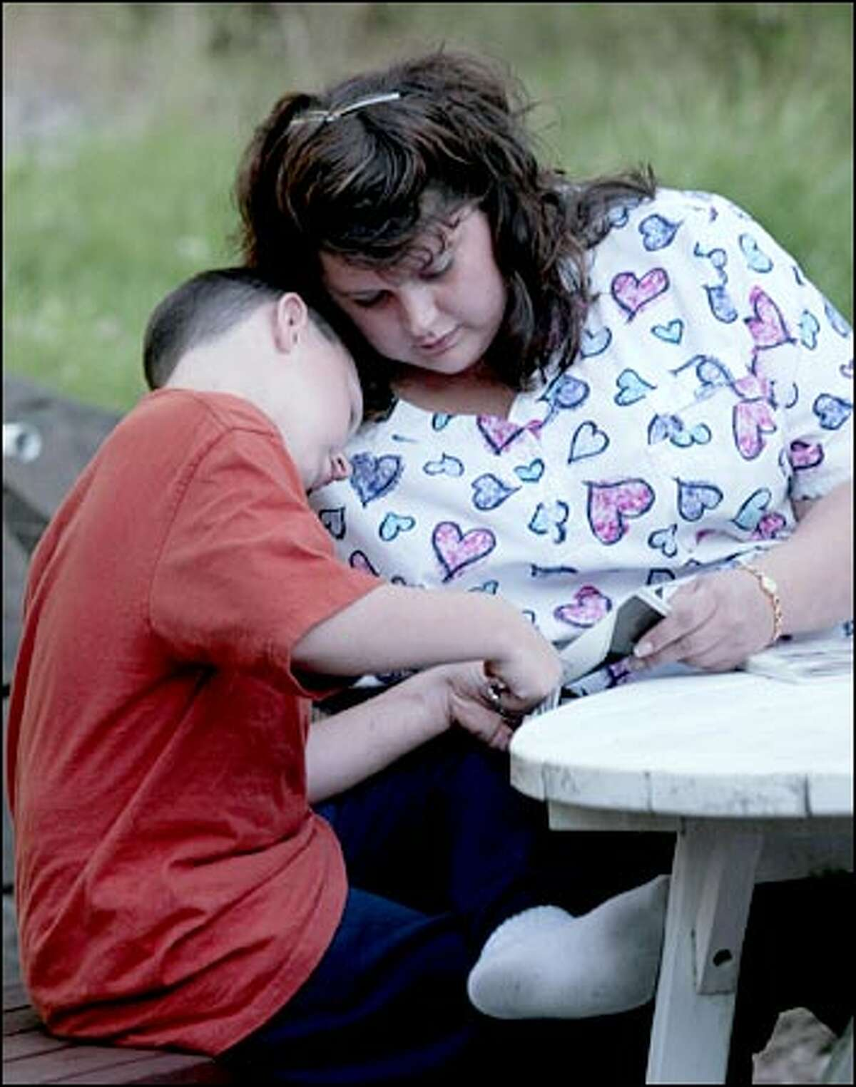 Christopher Bateman and his mom, Michelle, cut out a paper airplane. Bateman was accused by Dr. Kenneth Feldman of intentionally poisoning her son. Bateman lost custody of her son until a CPS inquiry cleared her.
