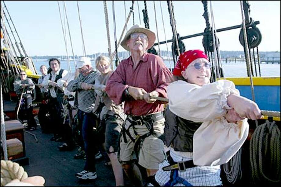 Wendy Joseph, front, and other members of the Lady Washington crew hold out the jib boom as the ship gets under way. Photo: Gilbert W. Arias/Seattle Post-Intelligencer