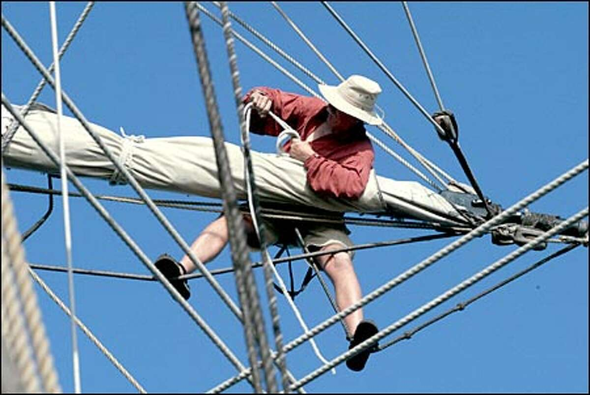 Using foot ropes for support, sailor Gary Thomas unties a sail as the Lady Washington gets under way in Boundary Bay off Blaine.
