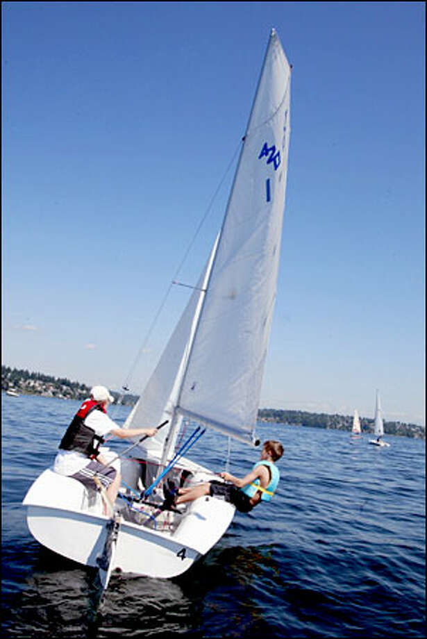 Einar Snorrason, 13, of Iceland, and James Tyson, 12 of Bethesda, Md., sail on Lake Washington. Both boys are visiting grandparents for the summer and joined the Sail Sand Point sailing camp. Photo: Meryl Schenker/Seattle Post-Intelligencer