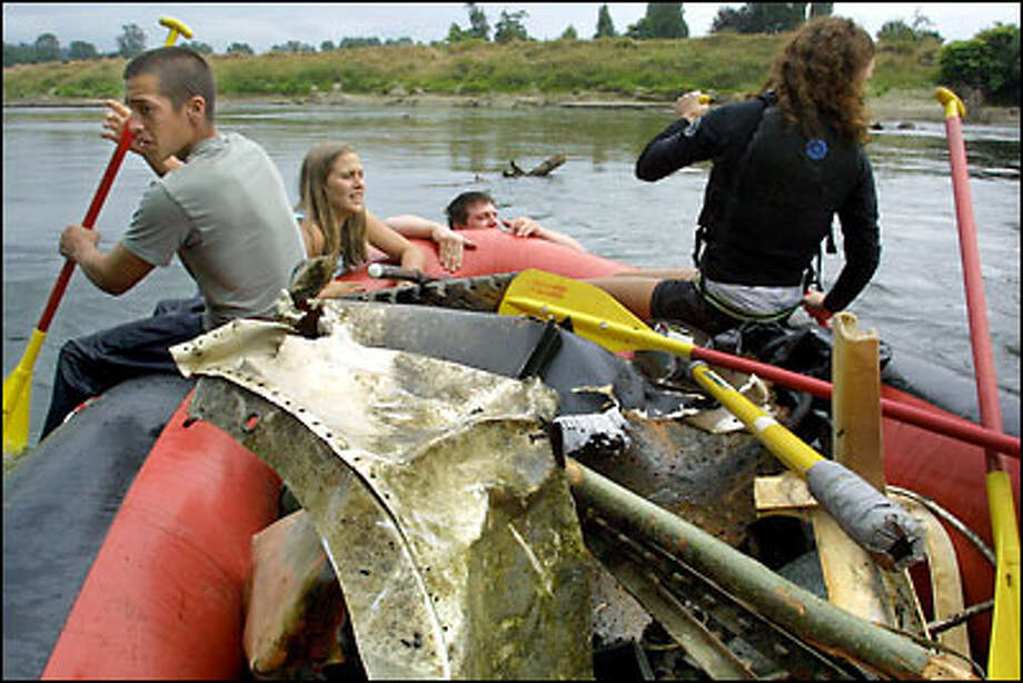 Volunteers from Friends of the Trail, a non-profit organization that performs public land cleanups, maneuver their raft through snags on the Snoqualmie River near Carnation. Photo: Melina Mara/Seattle Post-Intelligencer