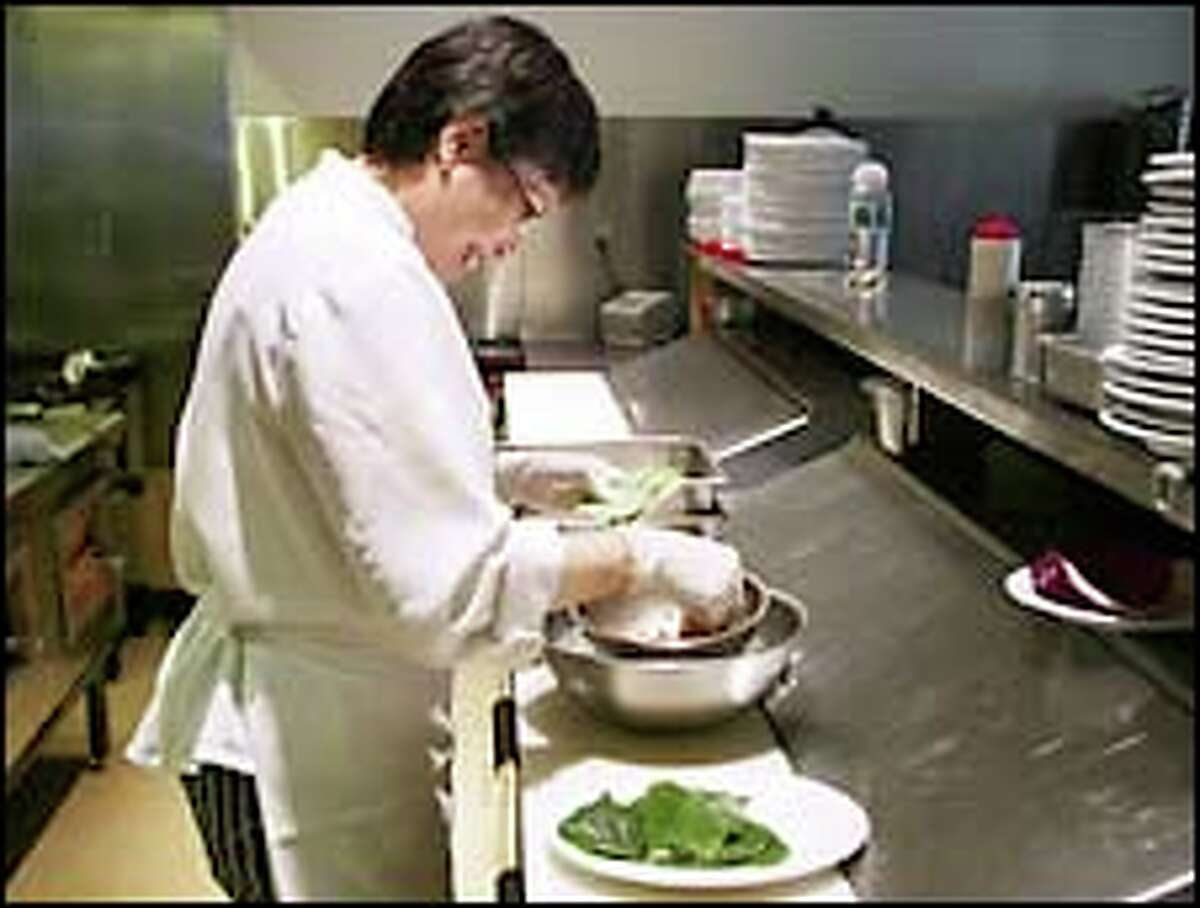 Sophie Bahn prepares Bo La Lot Beef in the kitchen of Monsoon, which she owns with her brother, Eric, and sister, Yen.