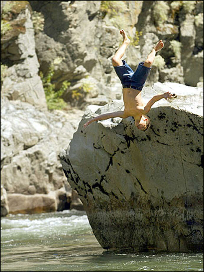 Jordan Salcedo, 12, of Marysville does a backflip into the icy waters of the Stillaguamish River near the Granite Falls Fish Ladder. Photo: Meryl Schenker/Seattle Post-Intelligencer