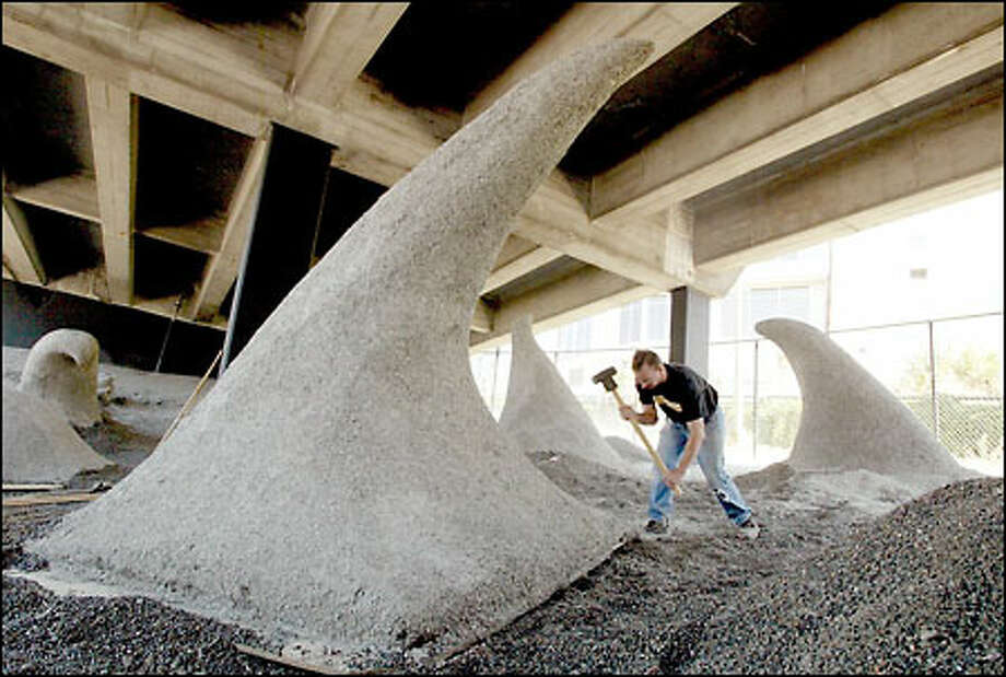 "Michael Graham, a carpenter for Pacific Studios, works on installing ""Wave Rave Cave"" under the state Route 99 viaduct at the corner of Western Avenue and Bell Street in Seattle. Photo: Meryl Schenker/Seattle Post-Intelligencer"