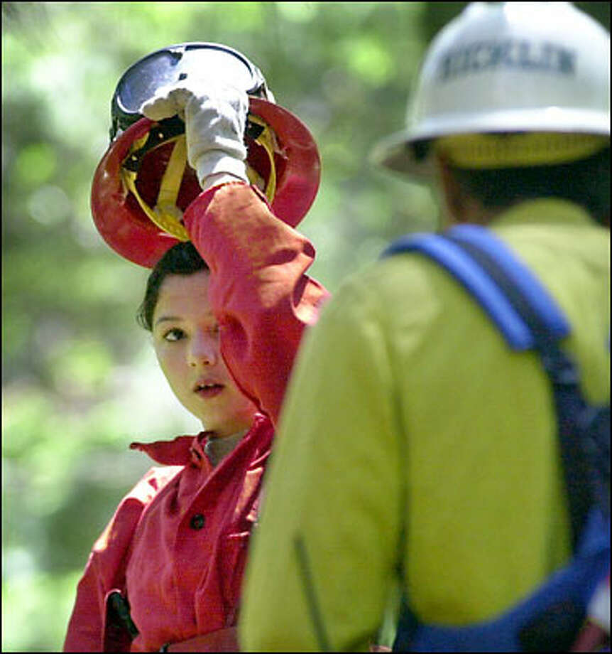 Crystal Galindo takes a breather as she listens to instructor Sid Hicklin while training June 10 with members of an all-girl firefighting team of juvenile offenders at the Naselle Youth Camp in Naselle. Photo: / Associated Press