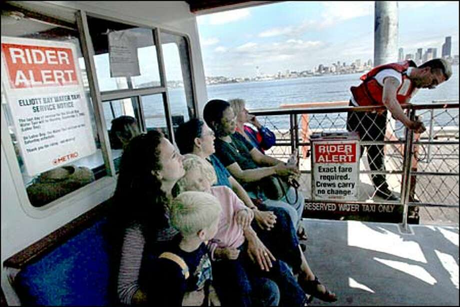 Herbert Auckland, right, closes a gate on the Elliott Bay Water Taxi. Madelyn Jansma, left, of Sammamish rides with her children, Andrew, 5, and Katy, 3. Photo: Paul Joseph Brown/Seattle Post-Intelligencer