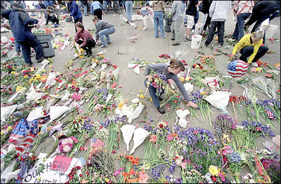 Hundreds of volunteers removed the flowers that were placed in the International Fountain at Seattle Center in memory of the victims of 9/11. The flowers were made into compost used to enrich a new memorial garden that will be dedicated Wednesday. It's part of the new landscaping in front of the recently finished Fisher Pavilion. Photo: P-I File