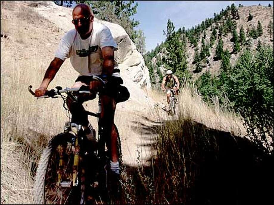 Two cyclists ride along a mountain ridge on Devils Gulch Trail near Cashmere. Photo: Melina Mara/Seattle Post-Intelligencer