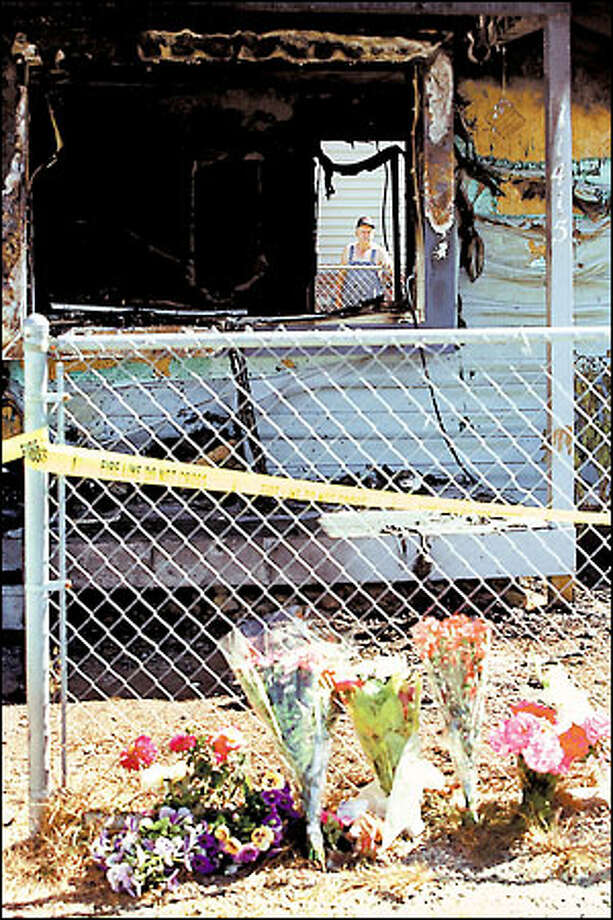 Clarence Bumgarner looks through the burned, broken window of his neighbors' Parkland home in Pierce County. Photo: Loren Callahan/Seattle Post-Intelligencer