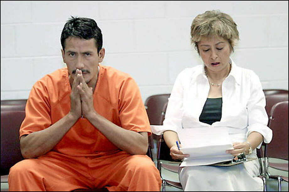 With interpreter Chely Tillson, Maximiliano Silerio Esparza sits in jail in Klamath Falls, Ore., accused of killing a Bellevue nun. Photo: Associated Press
