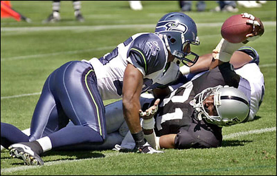 Raiders wide receiver Tim Brown flashes the ball after catching an 8-yard touchdown in front of Seahawks strong safety Reggie Tongue during the first quarter. Photo: / Associated Press
