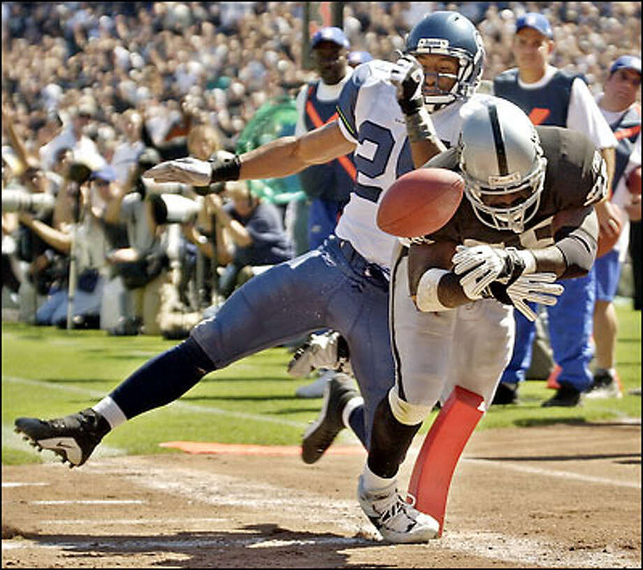 Raiders running back Randy Jordan scores a second-quarter touchdown from 7 yards out just before Seattle strong safety Reggie Tongue knocks the ball loose. Photo: / Associated Press