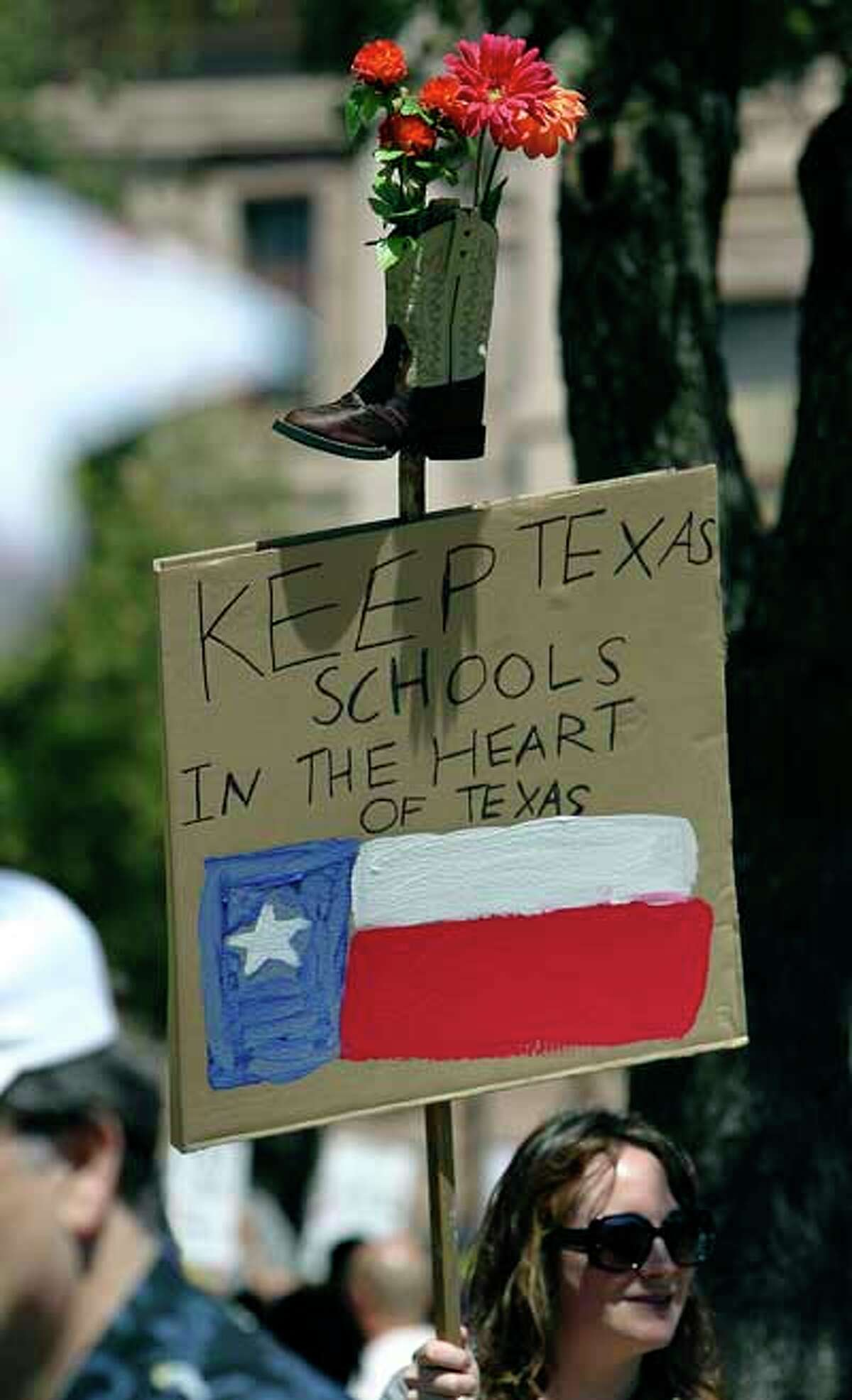 Marie Catrett holds a sign at a rally by thousands of educators and supporters at the Texas Capitol to decry looming budget cuts and elimination of jobs for educators on Saturday, Mar. 12, 2011. The sign was made by her daughter, Julia, who attends a school in Austin that is proposed to be closed. Kin Man Hui/kmhui@express-news.net
