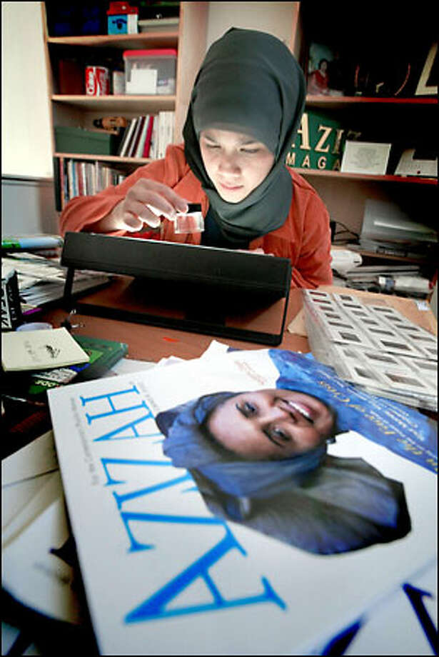 "Marlina Soerakoesoemah, creative director for Azizah magazine, edits fashions pictures for the magazine in her Redmond home office. ""You still hear horrible stories about (Muslim and Arab) people being profiled and harassed,"" she says. Photo: Dan DeLong/Seattle Post-Intelligencer"