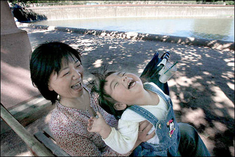 Akiyo Hernandez and her 1 1/2-year-old daughter, Alicia, play yesterday on a bench at Bellevue Downtown Park. Photo: Meryl Schenker/Seattle Post-Intelligencer
