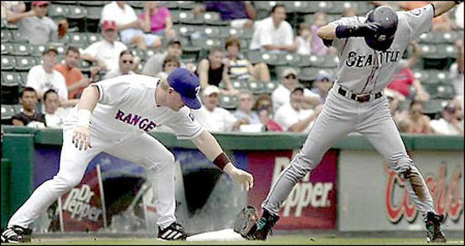 Rangers third baseman Hank Blalock loses his glove and fails to make the tag as Ichiro Suzuki slides into third with his 29th stolen base in the first inning. He scored on John Olerud's double. Photo: THE ASSOCIATED PRESS