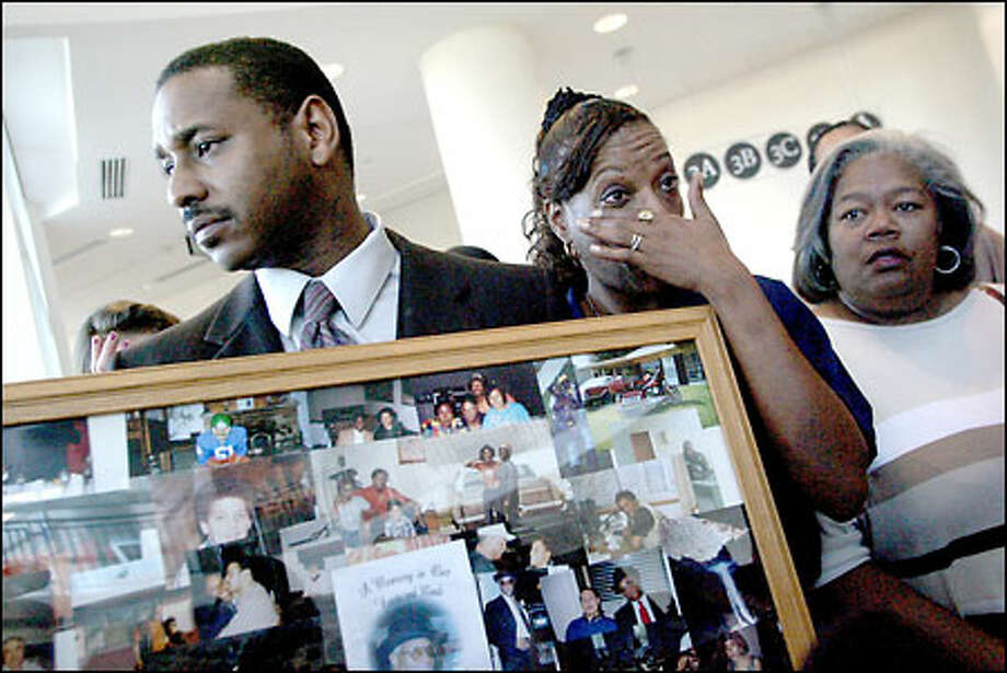 Robert Lee Thomas Jr. and his sister Robbie Thomas react to the inquest findings in Kent while holding photos that included images of their late father. Photo: Renee C. Byer/Seattle Post-Intelligencer