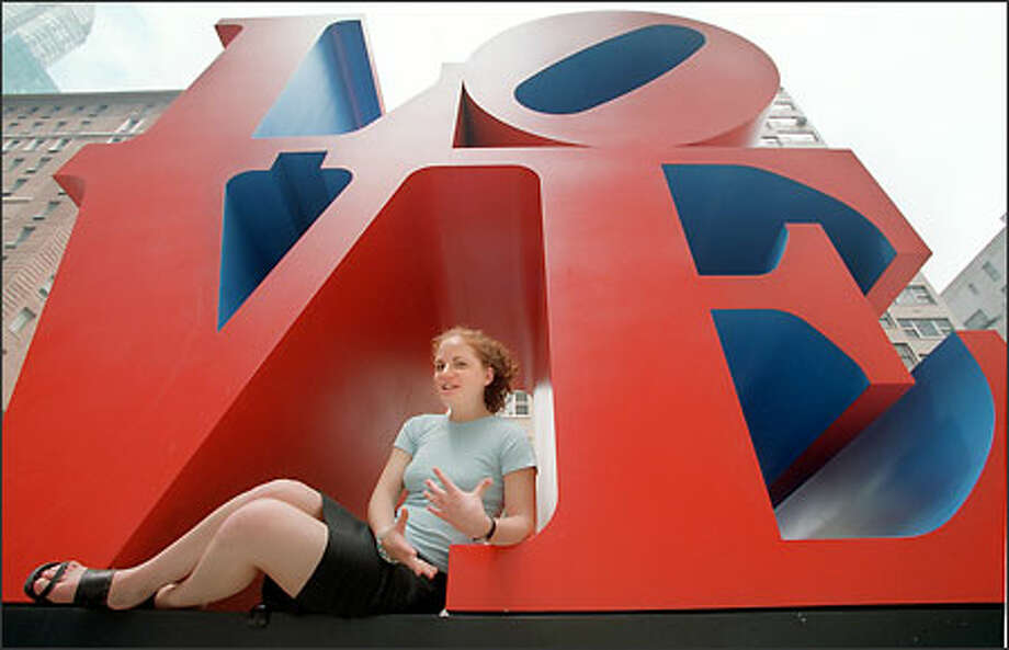 """Natalie Krinsky, a sex columnist at the Yale Daily News, sits under a """"LOVE"""" sculpture during a lunch break in New York. Photo: Associated Press"""