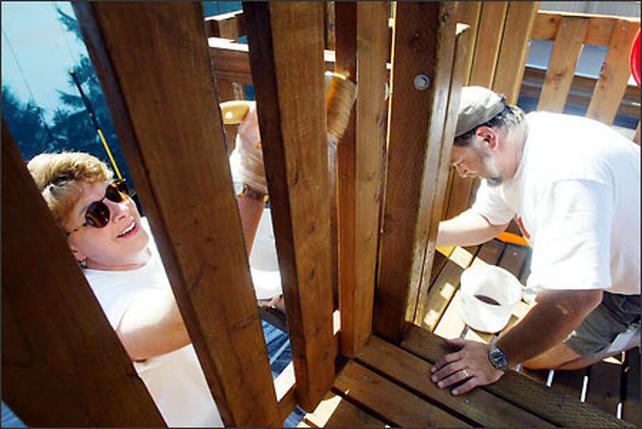 Brandee Warren, left, and Gary Grant seal a deck at Pinehurst Child Care Center in North Seattle, part of volunteer efforts around the city Friday in support of United Way. Photo: Renee C. Byer/Seattle Post-Intelligencer
