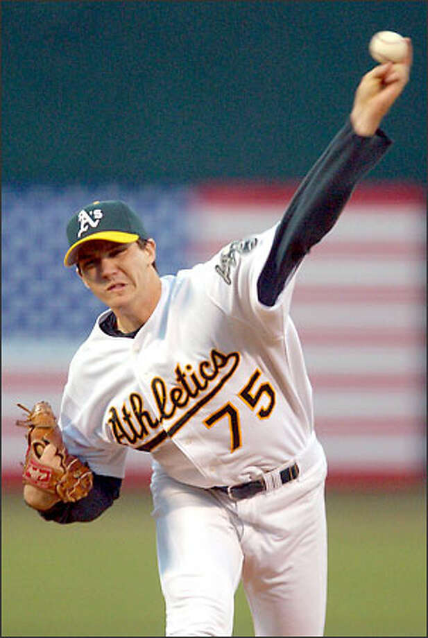 Oakland Athletics starting pitcher Barry Zito lobs one to the Mariners in the first inning.  He held the M's hitless through seven innings. Photo: / Associated Press