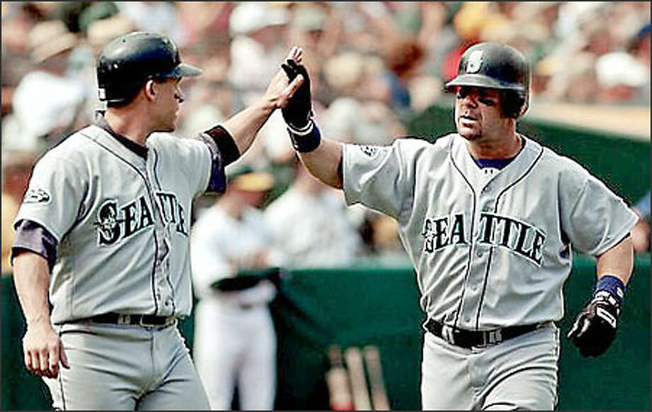 Edgar Martinez, right, is congratulated by Bret Boone after hitting a two-run homer in the third inning. Boone, who was in a 0-for-12 slump, had three hits and drove in two runs. Photo: THE ASSOCIATED PRESS