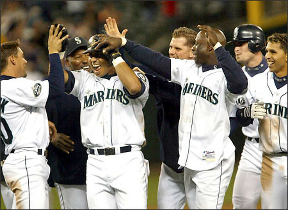 Carlos Guillen is congratulated by teammates after his 10th-inning single drove in Jose Offerman with the Mariners' winning run. Photo: Dan DeLong/Seattle Post-Intelligencer