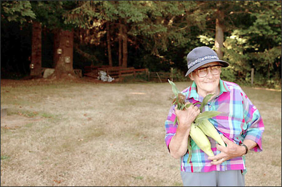 Gertrud Rohrbach in her Port Angeles garden with some of her homegrown corn. Rohrbach sells her fruit, vegetables and flowers at her weekly Gertie's Farmers Market. Photo: Meryl Schenker/Seattle Post-Intelligencer