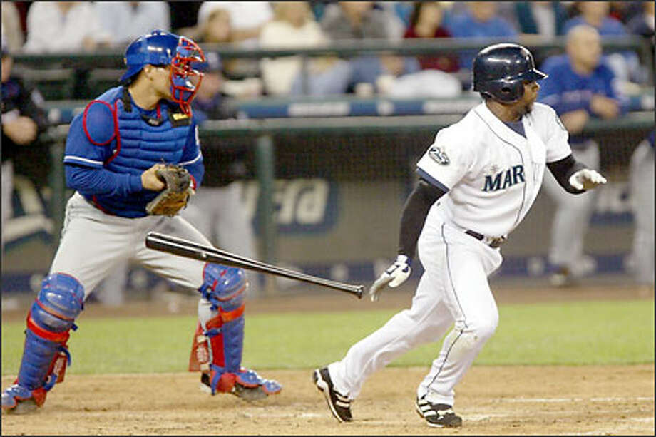 Desi Relaford singles to drive in Edgar Martinez in the third inning as Rangers catcher Ivan Rodriguez watches the flight of the ball, hoping to get a play at the plate. Photo: Dan DeLong/Seattle Post-Intelligencer