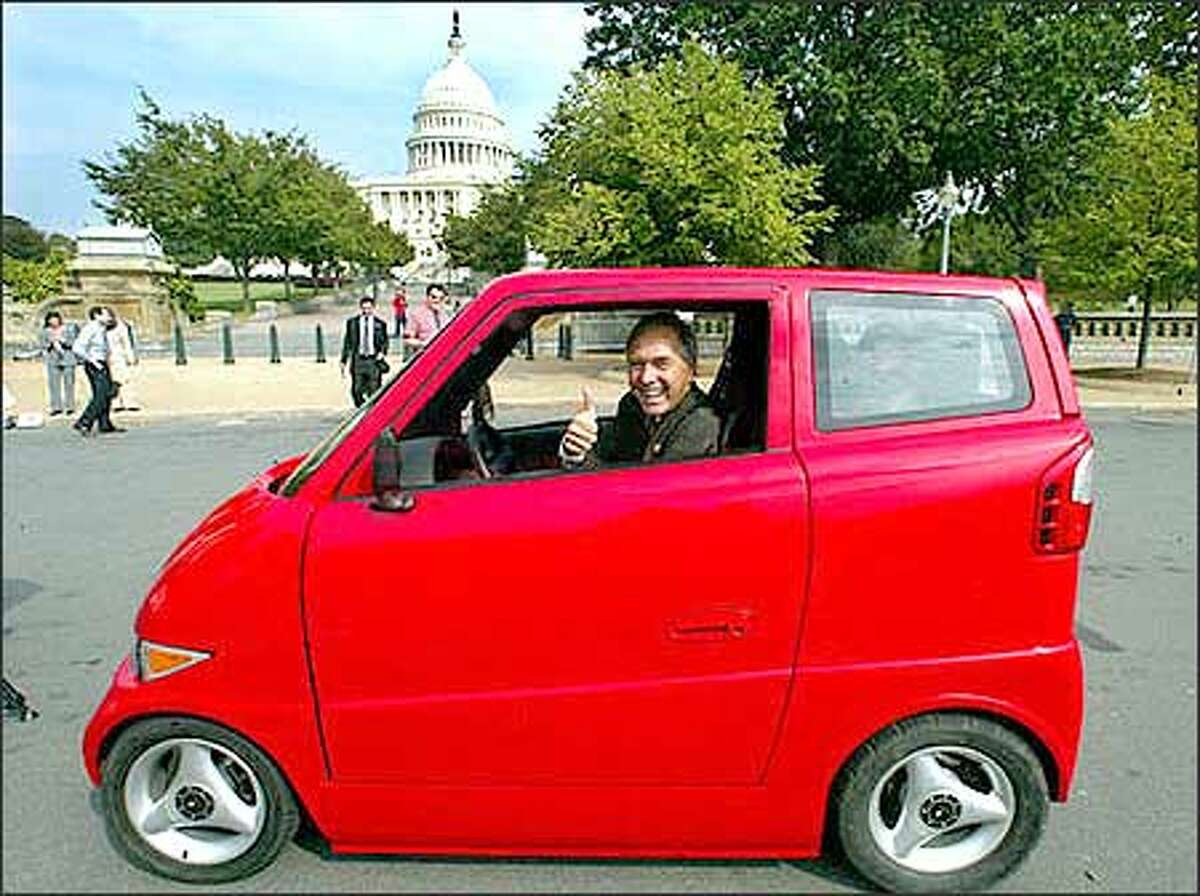 Rep. George R. Nethercutt, R- Wash., looks out from the electric and low-emission vehicle Tango Wednesday, Sept. 18, 2002, near the U.S. Capitol. The Tango, manufactured by Commuter Cars Corp. of Spokane, is narrower than a Honda Goldwing motorcycle and accelerates faster than a Dodge Viper. (AP Photo/Rick Bowmer)