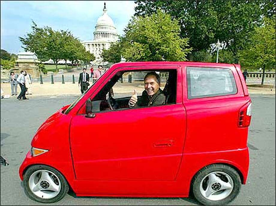 Rep. George R. Nethercutt, R- Wash., looks out from the electric and low-emission vehicle Tango Wednesday, Sept. 18, 2002, near the U.S. Capitol. The Tango, manufactured by Commuter Cars Corp. of Spokane, is narrower than a Honda Goldwing motorcycle and accelerates faster than a Dodge Viper. (AP Photo/Rick Bowmer) Photo: / Associated Press