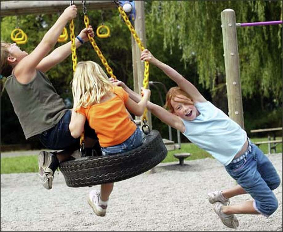 Who said going through a strike couldn't be fun? From left, Brittany Carl, 11 (Pine Lake Middle School); Stephanie Carl, 7 (Endeavour Elementary); and Emily Baer, 10 (Sunny Hills Elementary) play on a tire swing at Lake Sammamish State Park in Issaquah. The girls' teachers are on strike, and the trio went to the park Friday with their au pairs. Photo: Grant M. Haller/Seattle Post-Intelligencer