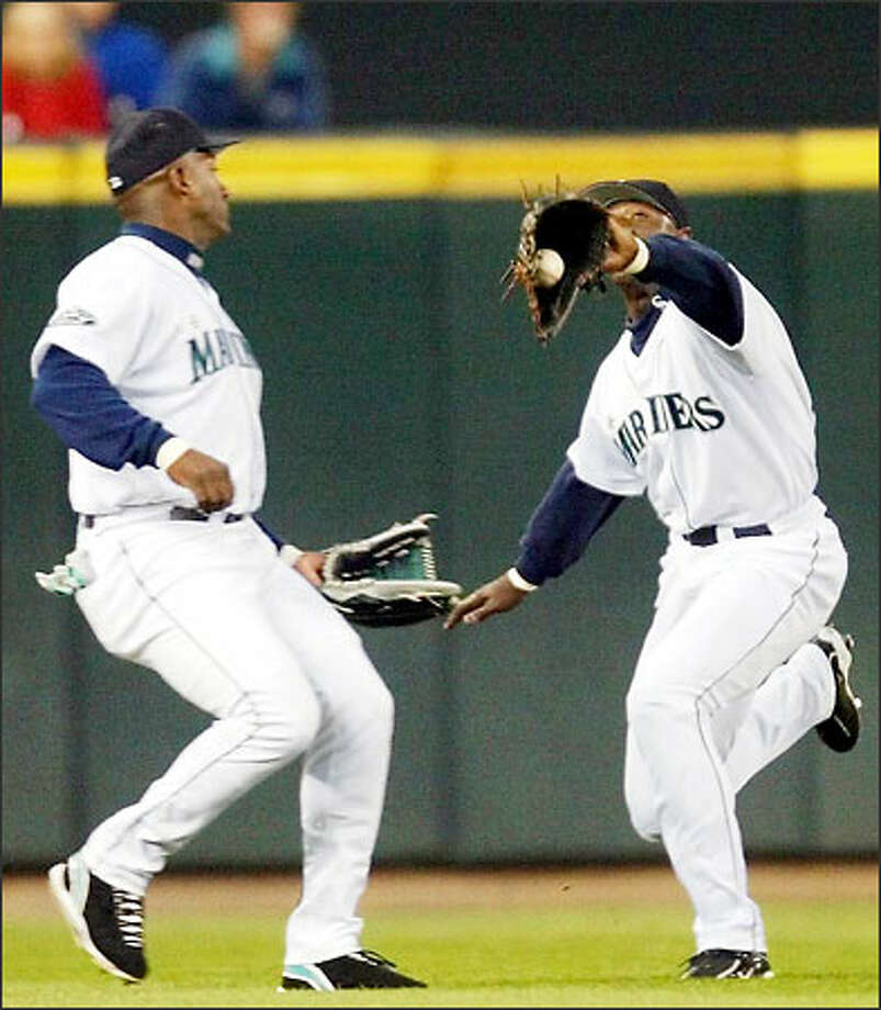 Mariners center fielder Mike Cameron snags a fly ball hit by Anaheim's Garrett Anderson in the first inning as Ruben Sierra looks on. Photo: Paul Kitagaki Jr./Seattle Post-Intelligencer